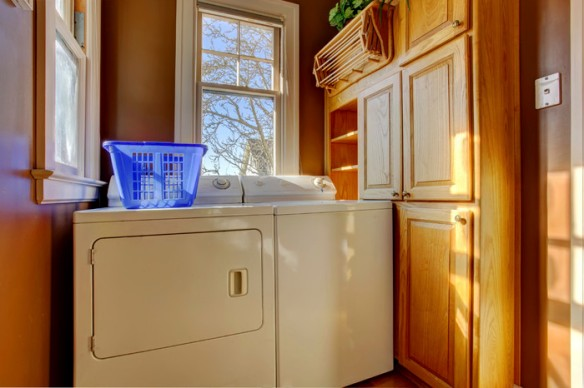 Small laundry room with wooden cabinet, white laundry appliances